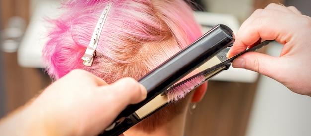 Nahaufnahme des friseurs, der das kurze rosa haar einer kundin mit einem haarglätteisen in einem schönheitssalon glättet