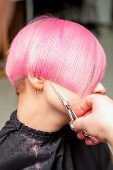 Nahaufnahme des friseurs, der kurzes rosa haar der jungen frau in einem friseursalon schneidet