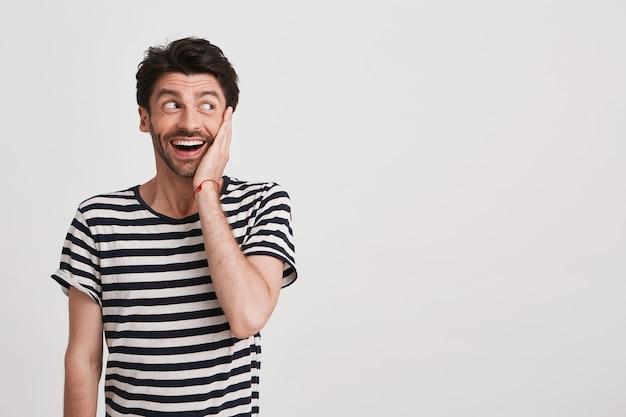 Nahaufnahme des fröhlichen hübschen jungen mannes mit borste trägt gestreiftes t-shirt fühlt sich glücklich isoliert auf weiß