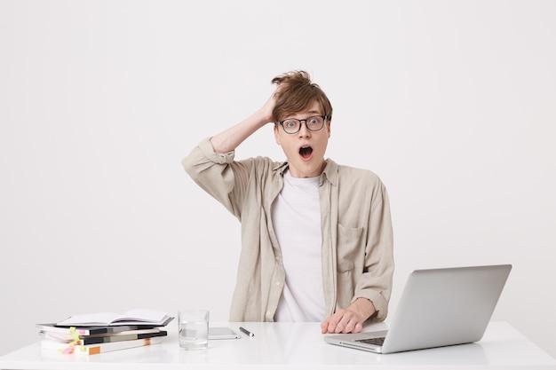 Nahaufnahme des fröhlichen jungen männlichen studenten mit klammern trägt beige hemdstudie unter verwendung des laptop-computers und der notizbücher, die am tisch lokalisiert über weißer wand sitzen