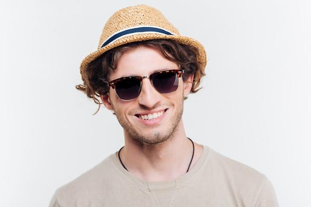 Nahaufnahme des fröhlichen jungen mannes im hut und in der sonnenbrille, die über weißem hintergrund lächeln