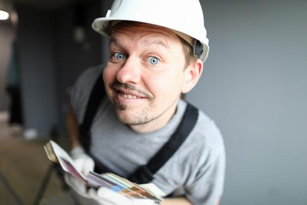 Nahaufnahme des fröhlichen männlichen arbeiters, der neugierig schaut