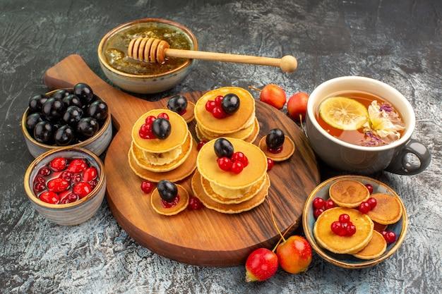 Nahaufnahme des frühstücks mit obstpfannkuchen und tee, serviert mit honig und kirschen