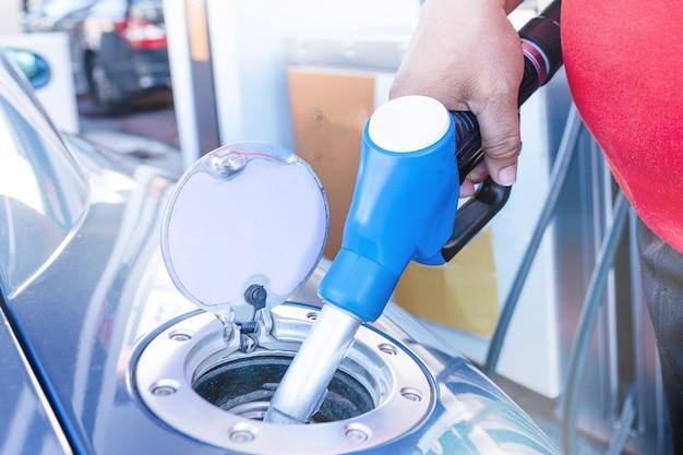 Nahaufnahme des füllens eines autos mit einem kraftstoff in einer station