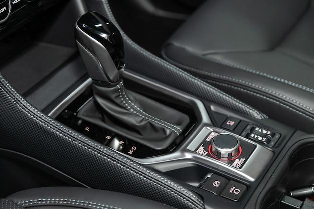 Nahaufnahme des gaspedalgriffs und der knöpfe mit moderner mittelkonsole mit kontrollen. automatikgetriebe des autos, autoinnenraum