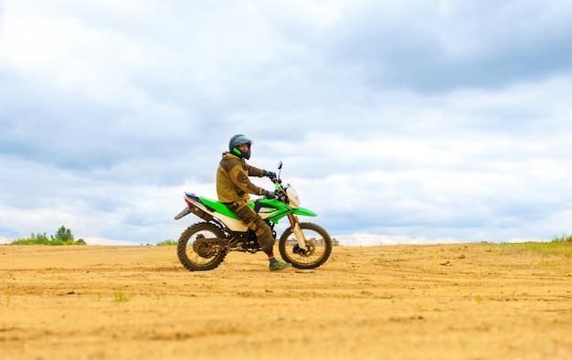 Nahaufnahme des gebirgsmotocrossrennens im sandweg in der tageszeit.