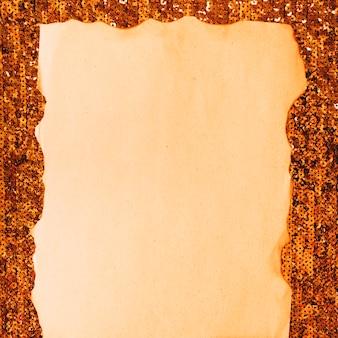 Nahaufnahme des gebrannten papiers gegen paillettengewebe