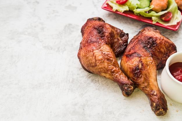 Nahaufnahme des gebratenen hühnerbeins mit soße und salat auf konkretem hintergrund