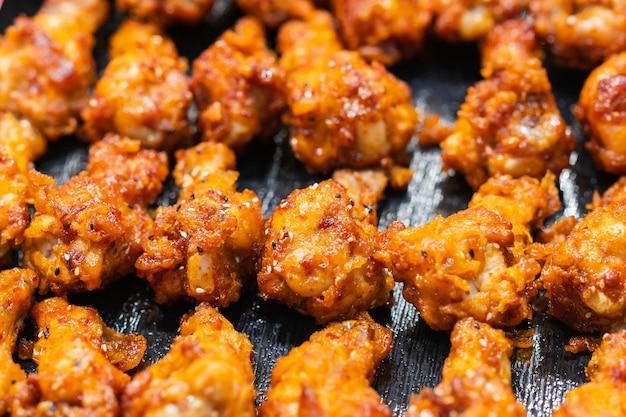 Nahaufnahme des gebratenen hühnertrommelstocks mit knoblauch und pfeffer, thailändischer straßenlebensmittelmarkt