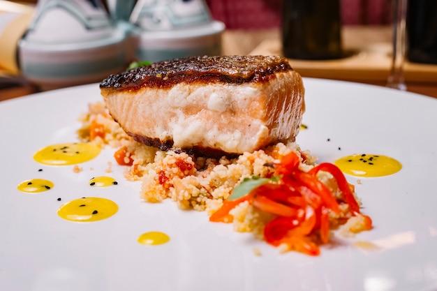 Nahaufnahme des gegrillten fischfilets, das oben auf dem couscous-salat mit paprika serviert wird