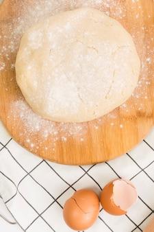 Nahaufnahme des gekneteten teigs auf hölzernem brett und defekter eierschale