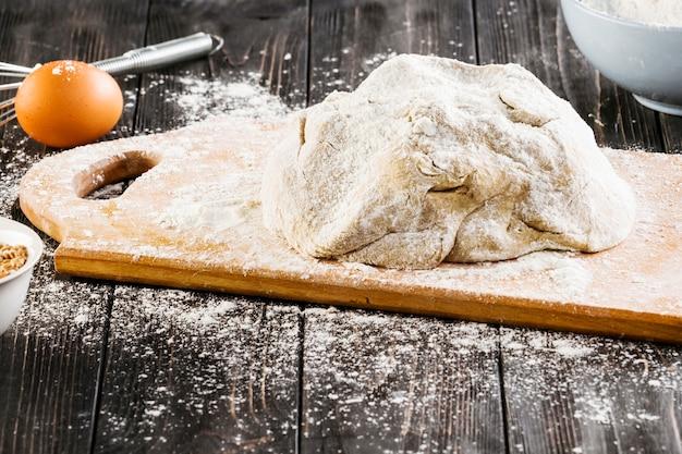 Nahaufnahme des gekneteten teigs mit verbreitetem mehl auf hackendem brett