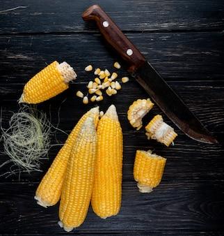 Nahaufnahme des gekochten ganzen und geschnittenen maissamens der körner mit seide und messer auf schwarzer oberfläche