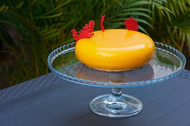 Nahaufnahme des gelben modernen runden kuchens auf glasigem stand