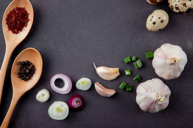Nahaufnahme des gemüses als zwiebel-knoblauch-frühlingszwiebelei und gewürze auf kastanienbraunem hintergrund mit kopienraum