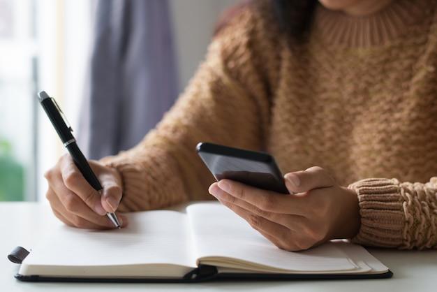 Nahaufnahme des geschäftsfrauplanungszeitplans unter verwendung des smartphone