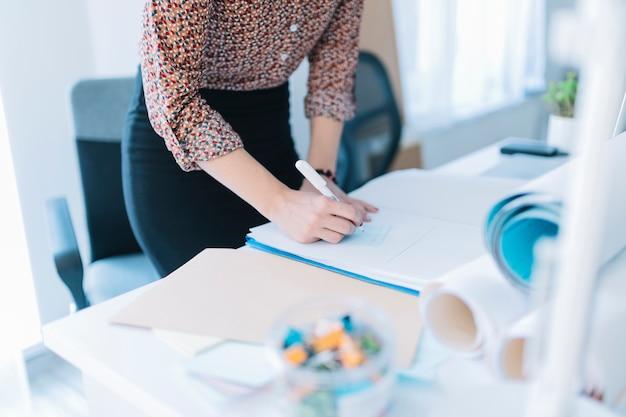 Nahaufnahme des geschäftsfrauschreibens auf klebender anmerkung im büro