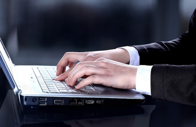 Nahaufnahme des geschäftsmannes, der auf laptop-computer schreibt?