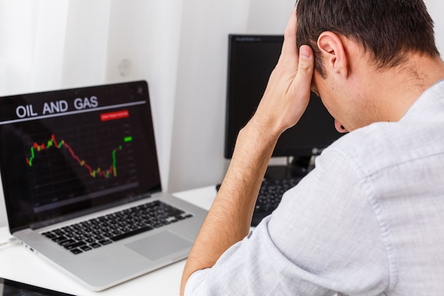 Nahaufnahme des geschäftsmannes, der diagramm auf dem laptop am arbeitsplatz im büro analysiert