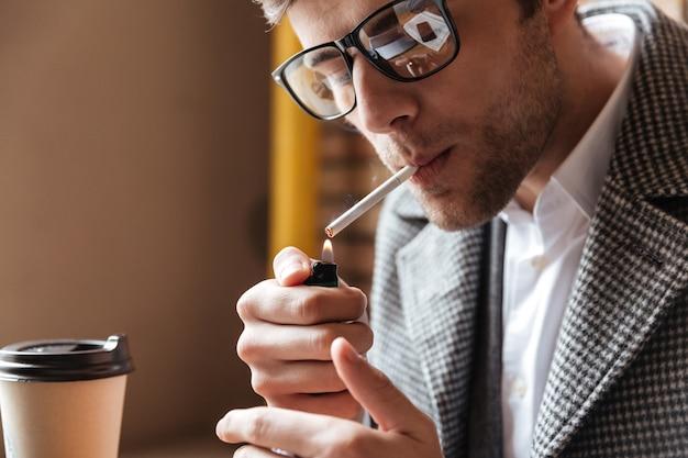 Nahaufnahme des geschäftsmannes in den brillen, die durch tabelle sitzen