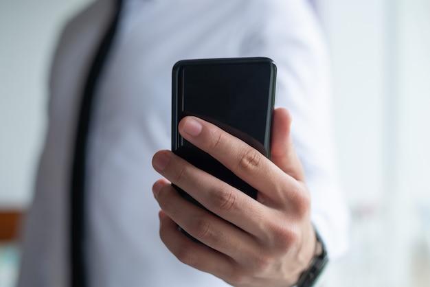 Nahaufnahme des geschäftsmannes intelligentes telefon halten
