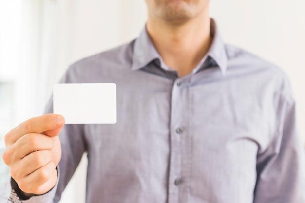 Nahaufnahme des geschäftsmannes leere weiße visitenkarte zeigend