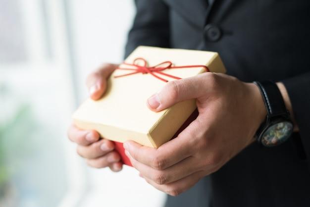 Nahaufnahme des geschäftsmannes mit der armbanduhr, die geschenkbox hält
