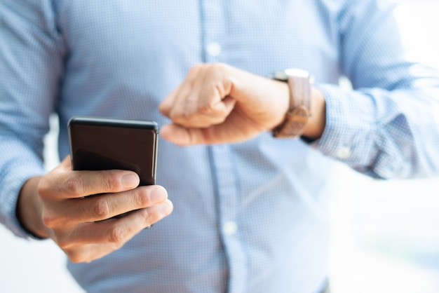 Nahaufnahme des geschäftsmannes smartphone halten und zeit überprüfend