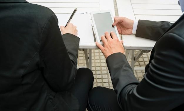 Nahaufnahme des geschäftsmannes und der geschäftsfrau, die intelligentes telefon halten und auf papier an draußen schreiben