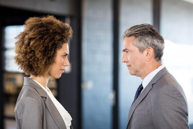 Nahaufnahme des geschäftsmannes und der geschäftsfrau, die vertraulich im büro stehen