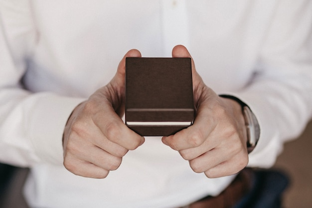 Nahaufnahme des geschenks auf männlichen händen. mann im weißen hemd. nicht erkennbarer mann, der braune geschenkbox hält. besonderes tages- und festveranstaltungskonzept. 2 männerhände mit kopierraum.