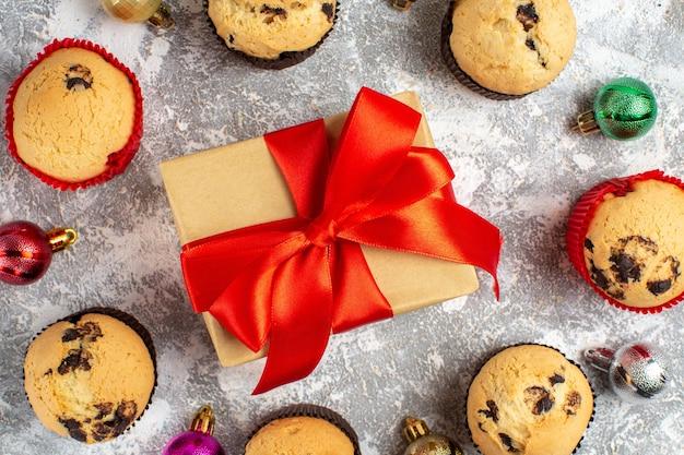Nahaufnahme des geschenks mit rotem band zwischen frisch gebackenen, köstlichen kleinen cupcakes und dekorationszubehör auf der eisoberfläche