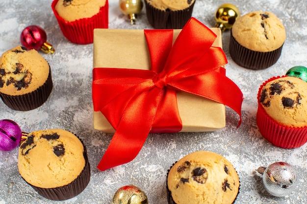 Nahaufnahme des geschenks mit rotem band zwischen frisch gebackenen leckeren kleinen cupcakes und dekorationszubehör auf dem eistisch