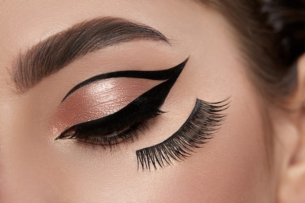 Nahaufnahme des geschlossenen auges der frau mit eyeliner und falschen wimpern u