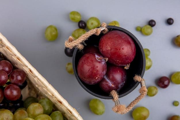Nahaufnahme des geschmacks könig pluots in schüssel mit trauben in korb und traubenbeeren auf grauem hintergrund