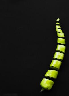 Nahaufnahme des geschnittenen grünen paprikapfeffers auf schwarzer oberfläche