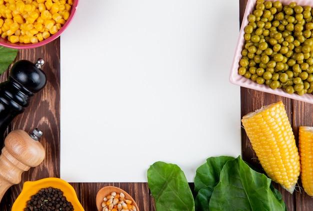 Nahaufnahme des geschnittenen mais mit maissamen schwarzer pfeffersamen grüner erbsenspinat und notizblock auf holzoberfläche mit kopienraum