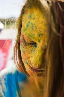 Nahaufnahme des gesichtes der frau bedeckt mit gelber holi farbe