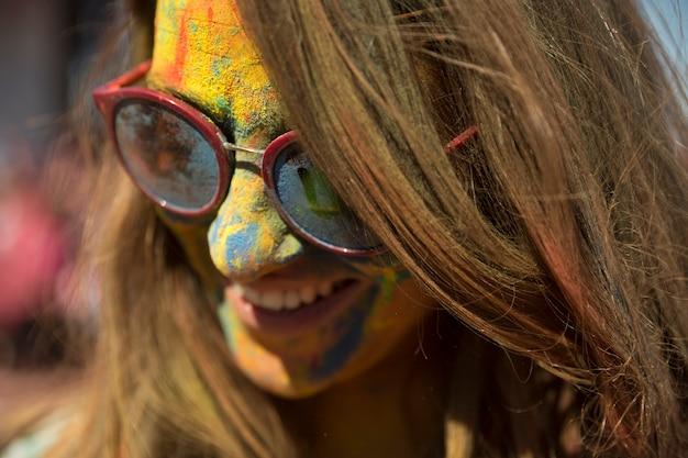 Nahaufnahme des gesichtes der frau bedeckt mit holi farbtragenden brillen