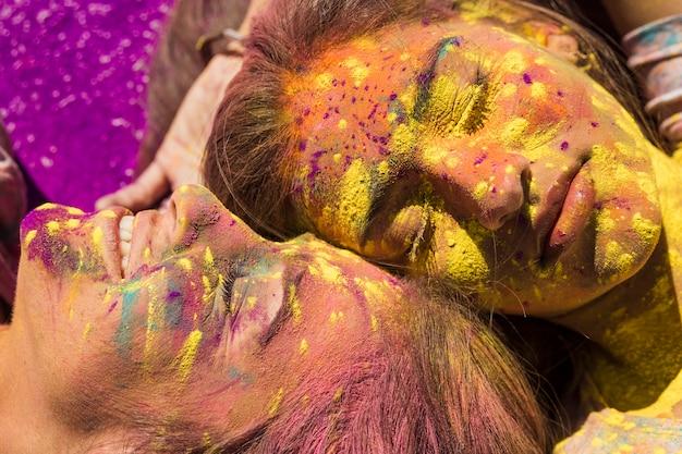 Nahaufnahme des gesichtes der jungen frauen bedeckt mit holi farbe