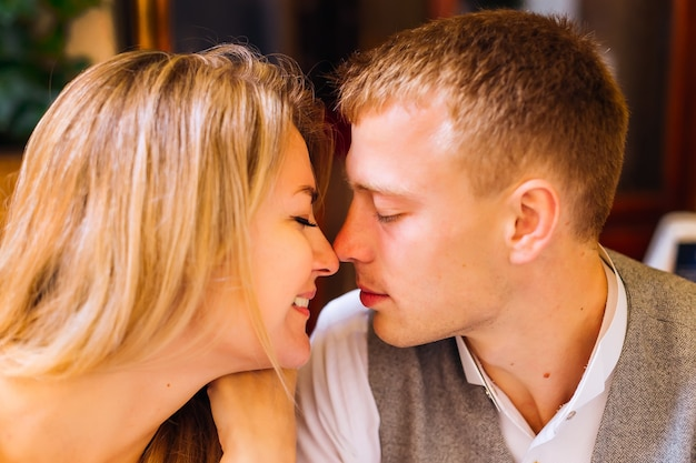 Nahaufnahme des gesichts des kerls und des mädchens, das sie die augen geschlossen haben und das profil küssen wollen