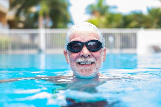Nahaufnahme des gesichts eines älteren oder reifen mannes, der schwimmt und spaß am pool hat - training und allein genießen