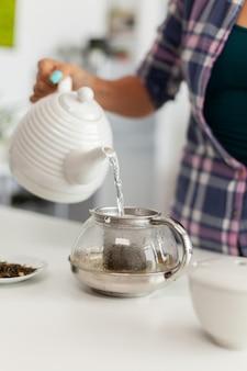 Nahaufnahme des gießens von heißem wasser über natürliche aromatische kräuter, um tee zuzubereiten