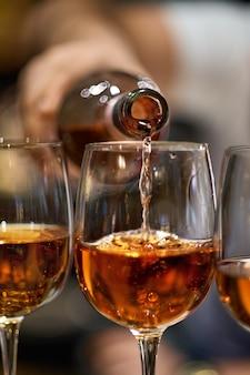 Nahaufnahme des gießens von rotwein in glas
