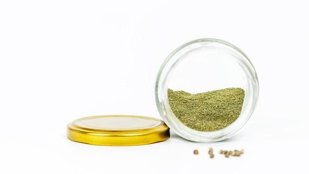 Nahaufnahme des glasgefäßes mit haschisch und cannabissamen auf weiß.