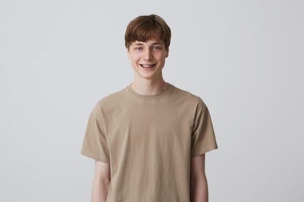 Nahaufnahme des glücklichen gutaussehenden jungen mannes mit kurzem haarschnitt und blauen augen trägt beige t-shirt