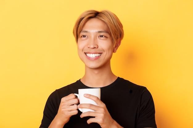 Nahaufnahme des glücklichen lächelnden hübschen blonden asiatischen kerls