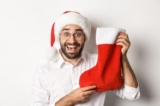 Nahaufnahme des glücklichen mannes, der weihnachten feiert, geschenke in der weihnachtssocke erhält und aufgeregt schaut, weihnachtsmütze und brille tragend