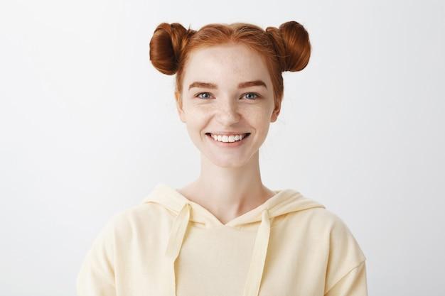 Nahaufnahme des glücklichen rothaarigen teenager-mädchens, das mit weißen zähnen lächelt