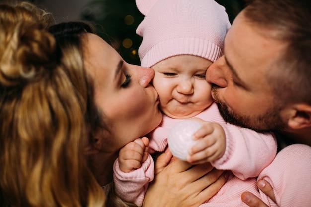 Nahaufnahme des glücklichen vaters und der mutter, die ihr süßes baby küssen. elternschafts- und familienkonzept